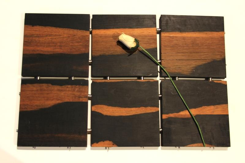 Flor de pétalos de madera sobre losetas de tapiz de ébano